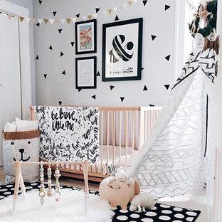 Foto di una piccola cameretta per neonati neutra scandinava con pareti bianche, moquette e pavimento nero