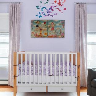 Exemple d'une chambre de bébé tendance avec un mur violet, un sol en bois brun et un sol marron.