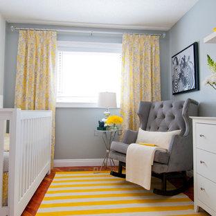 Diseño de habitación de bebé neutra clásica renovada, pequeña, con paredes grises y suelo de madera en tonos medios