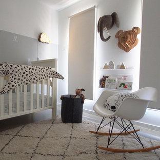 Idées déco pour une chambre de bébé contemporaine de taille moyenne avec un mur blanc et béton au sol.