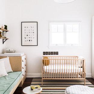 Idéer för ett litet modernt babyrum, med vita väggar, mörkt trägolv och brunt golv