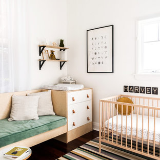 Photo of a small scandinavian nursery for boys in Perth with white walls, dark hardwood floors and brown floor.