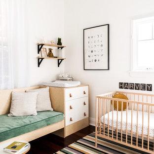Idée de décoration pour une petit chambre de bébé garçon nordique avec un mur blanc, un sol en bois foncé et un sol marron.