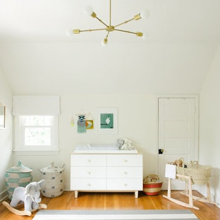 Example of a mid-sized eclectic gender-neutral medium tone wood floor and brown floor nursery design in Nashville with white walls
