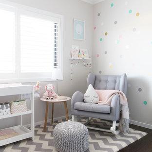 Imagen de habitación de bebé niña actual, de tamaño medio, con paredes grises y suelo de madera oscura