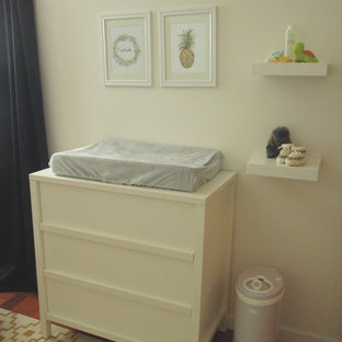 Small classic nursery in Vancouver with white walls, medium hardwood flooring and brown floors.