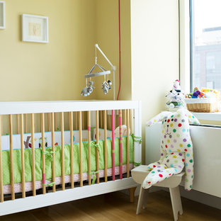 Design ideas for a scandinavian nursery for girls in New York with yellow walls and light hardwood flooring.