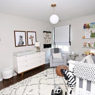 Example of a minimalist gender-neutral dark wood floor and brown floor nursery design in Other with gray walls