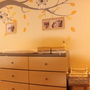 Imagen de habitación de bebé neutra clásica renovada, grande, con paredes amarillas, suelo de madera en tonos medios y suelo marrón