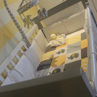 Diseño de habitación de bebé neutra tradicional renovada, grande, con paredes amarillas, suelo de madera en tonos medios y suelo marrón