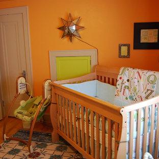 Nursery - traditional gender-neutral medium tone wood floor nursery idea in Other with orange walls