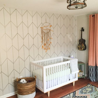Inspiration for a mid-sized midcentury modern gender-neutral medium tone wood floor nursery remodel with gray walls