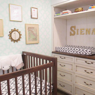 This is an example of a medium sized bohemian nursery for girls in New York with dark hardwood flooring and brown floors.
