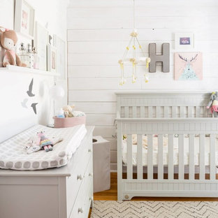 Medium sized country nursery for girls in Toronto with white walls and medium hardwood flooring.