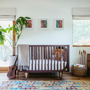 Example of a mid-sized 1950s gender-neutral medium tone wood floor nursery design in Los Angeles with white walls
