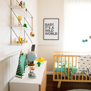 This is an example of a contemporary gender-neutral nursery in Other with beige walls, dark hardwood floors and brown floor.