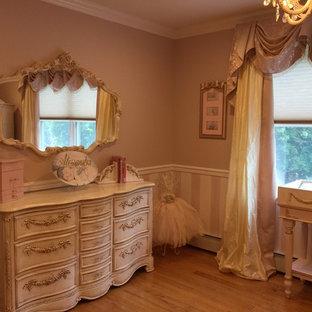 Imagen de habitación de bebé niña tradicional, grande, con paredes rosas y suelo de madera clara