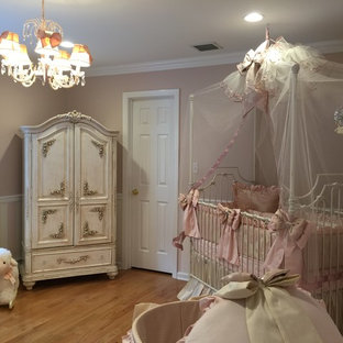 This is an example of a large traditional nursery for girls in New York with pink walls and light hardwood floors.