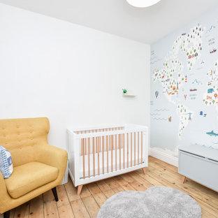 Idée de décoration pour une chambre de bébé neutre tradition de taille moyenne avec un mur blanc, un sol en bois brun et un sol marron.