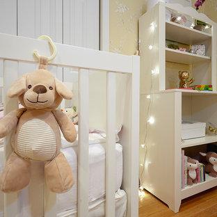 Diseño de habitación de bebé niña clásica renovada, pequeña, con paredes amarillas, suelo de madera clara y suelo amarillo