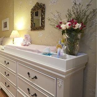 Idée de décoration pour une petit chambre de bébé fille tradition avec un mur jaune, un sol en bois clair et un sol jaune.
