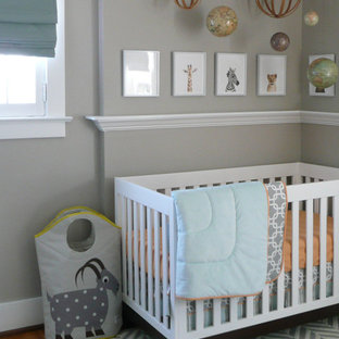 This is an example of a medium sized bohemian nursery for boys in Other with grey walls, medium hardwood flooring and brown floors.