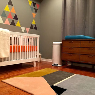 Medium sized modern nursery for boys in Philadelphia with grey walls, medium hardwood flooring and brown floors.