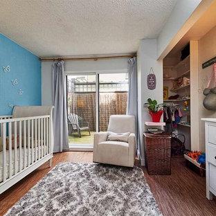 Cette photo montre une chambre de bébé neutre chic de taille moyenne avec un mur bleu, un sol en bambou et un sol marron.