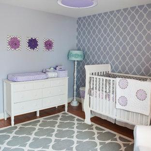 Diseño de habitación de bebé tradicional renovada, de tamaño medio, con paredes púrpuras y suelo de madera en tonos medios