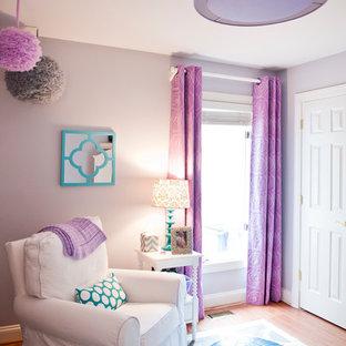 Aménagement d'une chambre de bébé contemporaine de taille moyenne avec un mur violet et un sol en bois clair.