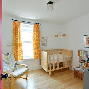 Foto de habitación de bebé neutra vintage, de tamaño medio, con paredes blancas y suelo de madera clara