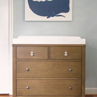 Design ideas for a small beach style gender-neutral nursery in DC Metro with blue walls and medium hardwood floors.