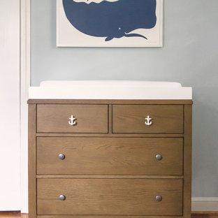 Diseño de habitación de bebé neutra marinera, pequeña, con paredes azules y suelo de madera en tonos medios