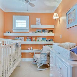 Diseño de habitación de bebé neutra costera, de tamaño medio, con parades naranjas, moqueta y suelo blanco