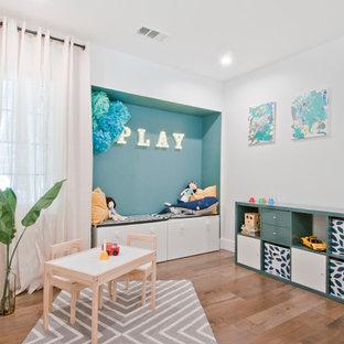 Foto de habitación de bebé neutra clásica renovada, de tamaño medio, con paredes grises, suelo laminado y suelo marrón