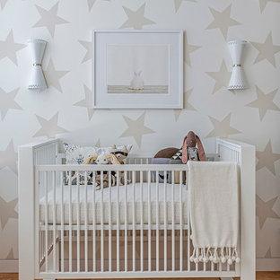 Diseño de habitación de bebé neutra contemporánea con paredes multicolor y suelo de madera clara