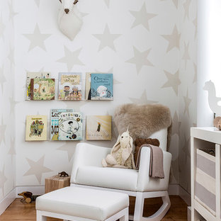 Contemporary gender neutral nursery in New York with multi-coloured walls and light hardwood flooring.