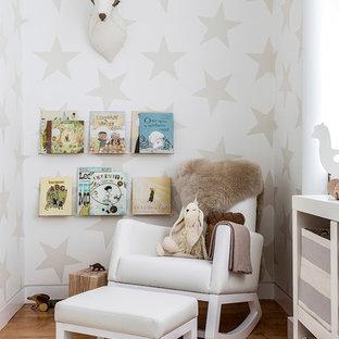 Modelo de habitación de bebé neutra contemporánea con paredes multicolor y suelo de madera clara
