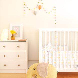 Ejemplo de habitación de bebé neutra clásica renovada, de tamaño medio, con paredes blancas y suelo de madera clara