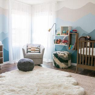 Modelo de habitación de bebé neutra tradicional renovada, grande, con paredes multicolor, suelo de madera oscura y suelo marrón
