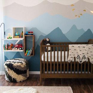 Modelo de habitación de bebé neutra clásica renovada, grande, con paredes multicolor, suelo de madera oscura y suelo marrón