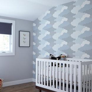 Diseño de habitación de bebé neutra retro, de tamaño medio, con paredes multicolor y suelo de madera oscura