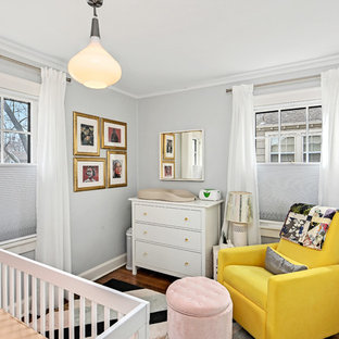 Example of an eclectic gender-neutral dark wood floor and brown floor nursery design in Kansas City with gray walls