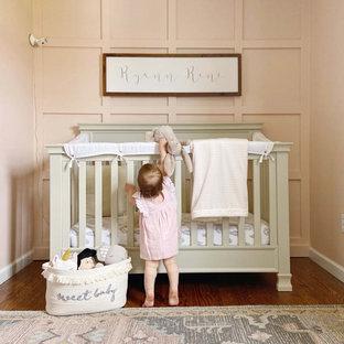 Small cottage girl medium tone wood floor nursery photo in Bridgeport with pink walls