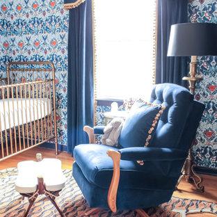 Immagine di una cameretta per neonato boho chic con pareti blu, pavimento in legno massello medio e carta da parati