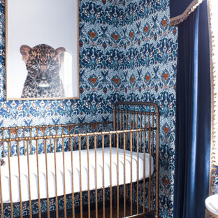 This is an example of an eclectic nursery for boys in Kansas City with blue walls, medium hardwood flooring and wallpapered walls.