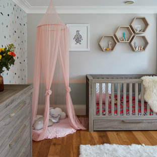 Inspiration for a large contemporary nursery for girls in Surrey with multi-coloured walls, medium hardwood flooring and brown floors.