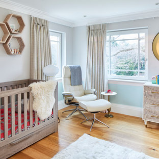 Photo of a large contemporary nursery in Surrey with blue walls and medium hardwood flooring.