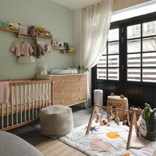 Photo of a large contemporary nursery for girls in London with green walls and grey floors.