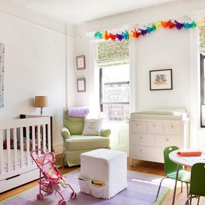 Nursery - large transitional girl medium tone wood floor nursery idea in New York with white walls